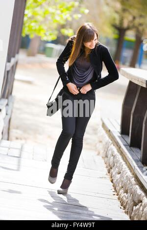 Attractive young woman is zipping pants Black jacket hurry rush rushing stumblin'in stumbling down street single - Stock Photo