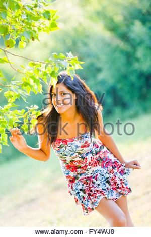 Nature-loving young woman standing stand bending over bend over joyful joy responsive response attractive healthy - Stock Photo