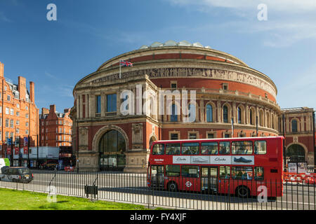 Iconic red double decker bus passes in front of Royal Albert Hall in Kensington, London, England. - Stock Photo