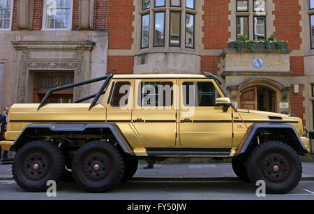 Gold painted Mercedes G63 AMG six wheel drive supercar costing £370,000 from Saudi Arabia parked in Mayfair, London - Stock Photo