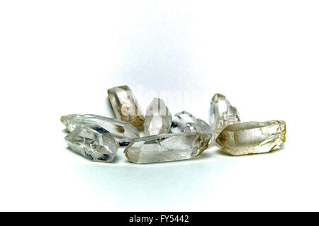 A group of eight clear quartz crystal points on white surface, not isolated. - Stock Photo