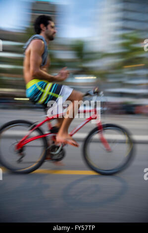 RIO DE JANEIRO - MARCH 6, 2016: A young Brazilian man rides his bicycle in motion blur on the Ipanema Beach beachfront - Stock Photo