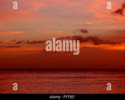 Red light of dusk over the ocean and sky as plane flies in the air on Oahu, Hawaii. - Stock Photo