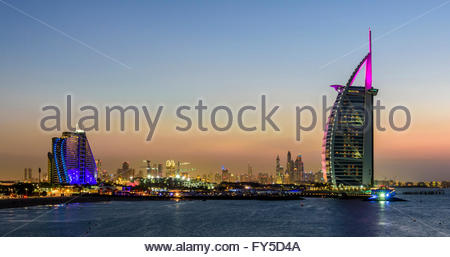 Sunset in Jumeirah, with on the left the Jumeirah Hotel, the Burj Al Arab and in the background the Marina of Dubai, - Stock Photo