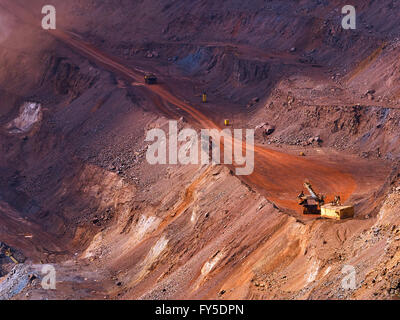 Top view of sunlit open-pit mine with quarry excavator loading iron ore to dump truck - Stock Photo