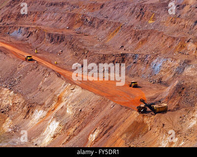 Top view of terraced open-pit mine with quarry excavator loading iron ore to dump truck - Stock Photo