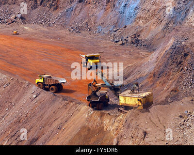 Quarry excavator load the iron ore to big dump truck in openpit mine with another two trucks waiting in queue - Stock Photo