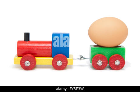 Colorful wooden model railway with an egg on a goods wagon, isolated - Stock Photo