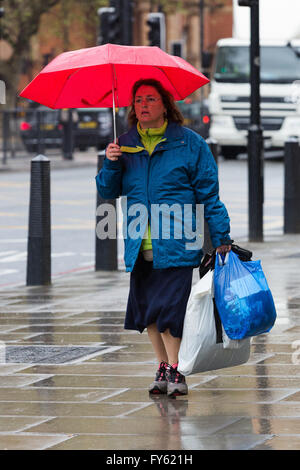 London, UK. 22nd April 2016. A woman walking with an umbrella in central London during rain and wet weather this afternoon. Credit:  London pix/Alamy Live News
