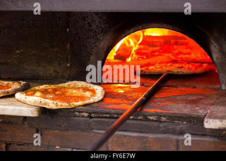 Looking inside a wood burning pizza oven at pizzas being baked in famous Italian restaurant in Naples, Pizzeria - Stock Photo