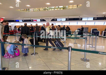 Departing passengers queue in departures check-in hall for check in Naples (Capodichino) International Airport (NAP). - Stock Photo