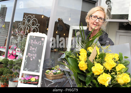 Woman holds a bouquet of flowers outside of Rolfe's Flowers in Cardiff, Wales. - Stock Photo