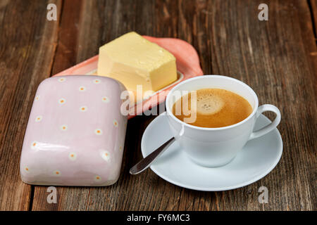 Coffe and butter on a dish on a brown wooden table - Stock Photo