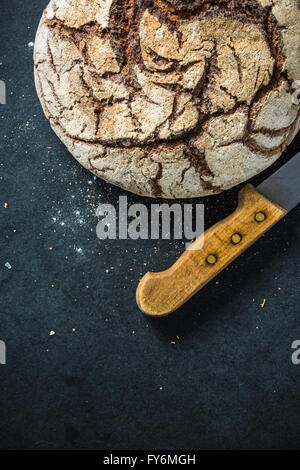 Artisan whole grain rye bread, on dark slate. Ingredients border background - Stock Photo