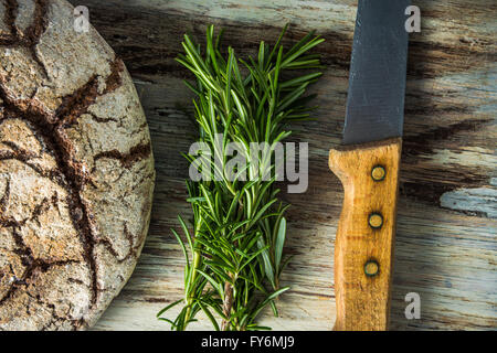 Artisan bread loaf, rosemary and knife, flat lay on wooden board - Stock Photo