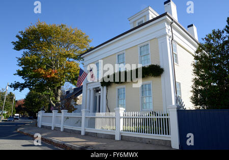 exterior of a large colonial style yellow house in the quaint town of Stonington Connecticut.  There are American - Stock Photo