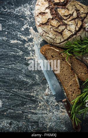 sliced rye artisan bread loaf, on dark slate from above - Stock Photo
