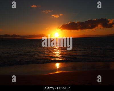 Sunset over the beach and ocean waters with boat sailing, clouds, Lanai and Molokai in the distance in Kaanapali, - Stock Photo