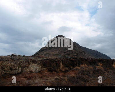 Rock cliff and mountain in the distance at Kaena Point on the island of Oahu, Hawaii - Stock Photo