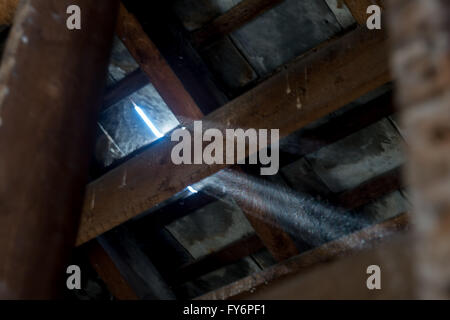 Sun beam through a broken slate during renovation of house interior stripped back to brickwork and wood beams - Stock Photo