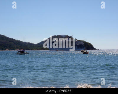 ZIHUATANEJO, MEXICO - JANUARY 10: Carnival Cruise ship rests in bay with small boats in forground during port of - Stock Photo
