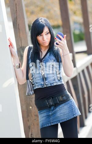 Teenager girl wearing denim clothes facing camera standing looking at handy mirror - Stock Photo