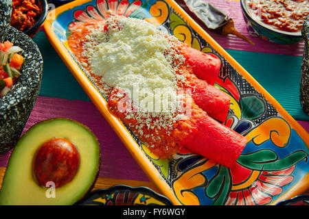 Red enchiladas Mexican food with guacamole and sauces on colorful table - Stock Photo