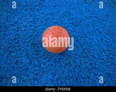 well used Orange golf ball on blue artificial turf - Stock Photo
