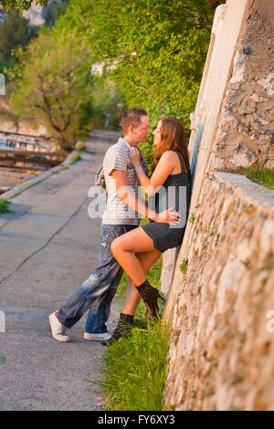 Sunset love young couple kissing sideview full length beautiful attractive teen stiletto attractive pretty pair - Stock Photo