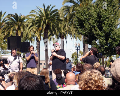 Filmmaker Michael Moore speaks in front of crowd at Justin Herman Plaza in San Francisco to promote a new movie - Stock Photo