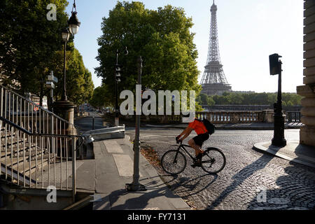 A man riding bicycle on the end of Pont Bir-Hakeim Bridge with Eiffel Tower in the background, Paris, France - Stock Photo