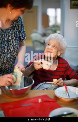 Woman, 89 years, and a social worker, 31 years, cooking as a pastime for the elderly, nursing home - Stock Photo