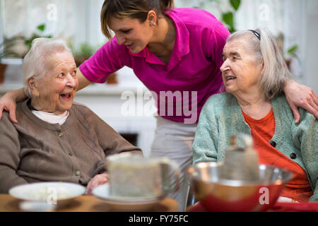 Two elderly women, 78 years and 88 years, and a carer for the elderly, 31 years, leisure activities in a nursing - Stock Photo