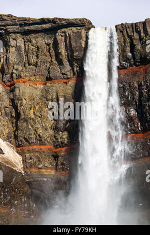 The Hengifoss waterfall in Iceland with red strata stripes - Stock Photo