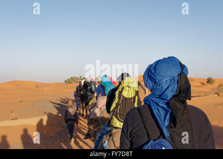 Camel trip in the evening with several people photographed from behind in the Erg Chebbi desert near Merzouga in Morocco.