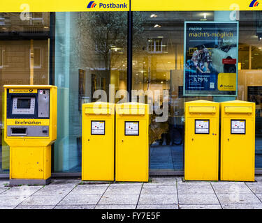 Stuttgart Postbank, post office with yellow stamp vending machines and post boxes, Germany - Stock Photo