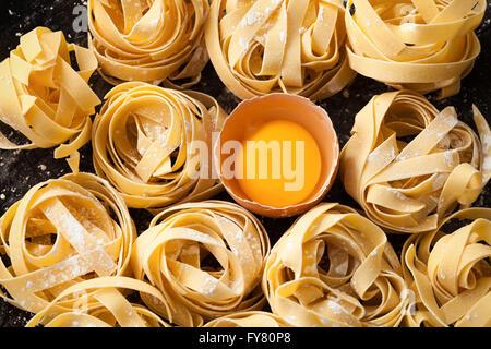 fettuccine pasta italian food still life rustic flat lay black background tagliatelle alfredo yolk close up macro - Stock Photo
