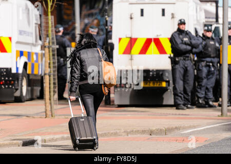 A woman wheels a suitcase towards a line of PSNI police officers in Belfast. - Stock Photo