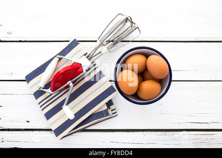 Vintage metal hand whisk with red body shot on retro white wooden background with blue and white striped napkin - Stock Photo