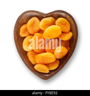 Dried apricots in heart shaped wooden bowl - Stock Photo