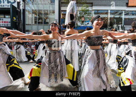 Close up of Japanese young women dance team in black and white costume formation dancing in shopping arcade at Yosakoi - Stock Photo