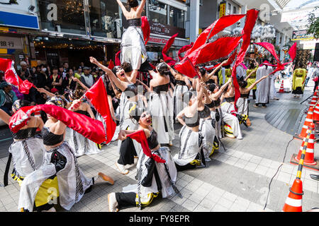 Japanese young women dance team in black and white costume formation dancing and swirling red streamers in shopping - Stock Photo