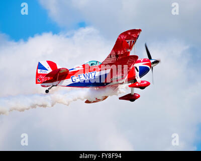 Pitts Special S-2S aerobatic biplane climbing and trailing white smoke - Stock Photo