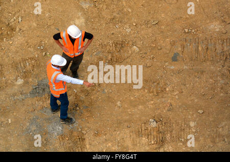 Aerial view of two unrecognized civil engineers inspecting construction site. Building development concept with - Stock Photo