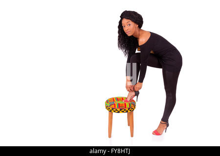 Beautiful African American woman putting her high heels shoes - Stock Photo