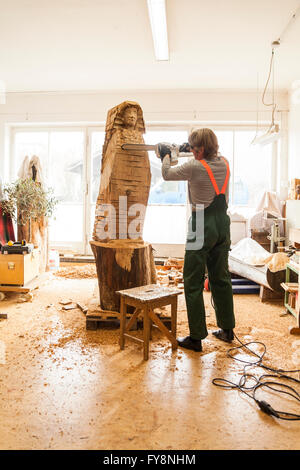 Wood carver in workshop working on sculpture with chainsaw - Stock Photo