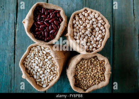 Four sacks of dried brown lentils, chickpeas and red and white beans on wood - Stock Photo