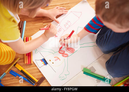 Brother and sister painting on floor - Stock Photo