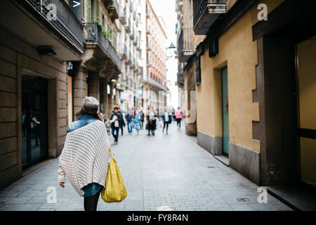 Spain, Barcelona, young woman walking in an alley - Stock Photo