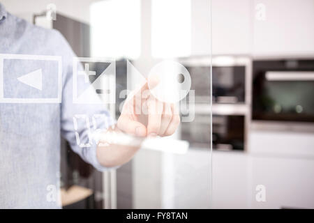 Man's hand using touchscreen of oven in his kitchen - Stock Photo